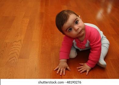 Cute baby sitting on hardwood floor