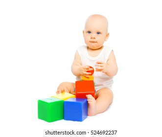 Cute baby sitting playing with colorful toys on a white background