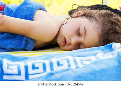 Cute baby is sleeping on the beach at summer day, wrapped in towel
