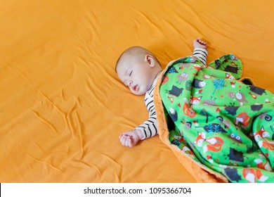 Cute baby sleeping on big bed covered with soft fleece blanket. High angle view, no retouch, natural light.