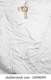 A cute baby sleeping on a huge bed with white sheets