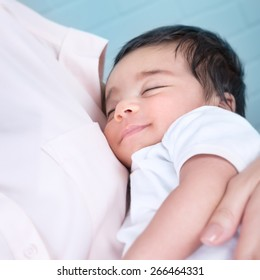 Cute baby sleeping on mothers hands, carefree and happy childhood, lovely new family, peace and relaxation concept