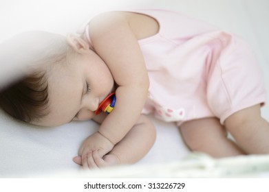 Cute baby sleeping with a pacifier