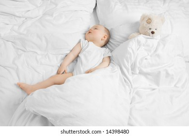 A cute baby sleeping with a teddy on a clean white bed