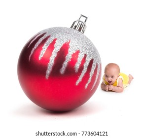 Cute Baby smiling at a Huge Christmas Ornament on white
