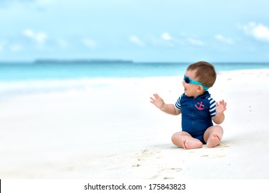 Cute baby smiling, sitting on white sandy tropical beach on Maldives, having vacation. With diving costume or swimwear, sunglasses.