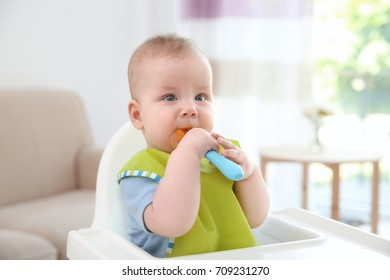 Cute baby with spoon sitting in kitchen