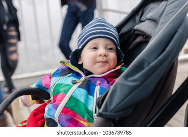 cute baby in stroller. child sitting in pram on city walk. laughing small boy enjoying his time in carriage outdoors. cheerful kid portrait.