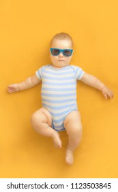 Cute baby with sunglasses lying on an orange dress wearing baby sailor suit with blue and white stripes and enjoying sunbathing