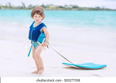 Cute baby with swimwear and life vest walking on the tropical beach with boogie board