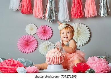 Cute baby tasting the birthday cake