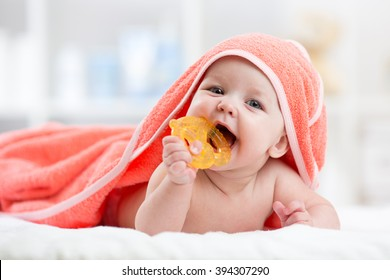 Cute baby with teether under a hooded towel after bath