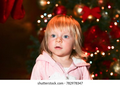 Cute baby Toddler blonde girl with big blue eyes dreaming about Santa and presents wearing pink pajama sitting over Christmas tree in room close up. Holiday season. Childhood. Happy Family. Christmas