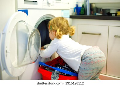Cute baby toddler girl taking clean clothes from the washing machine. Adorable child, healthy daughter helping mom with laundry.