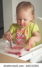 cute baby toddler learn to eat soup with spoon and spoil it around herself