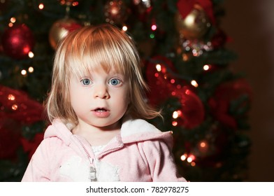 Cute baby Toddler surprised girl with big blue eyes looks at camera wearing pink pajama sitting over Christmas tree in room close up. Holiday season. Childhood. Happy Family.