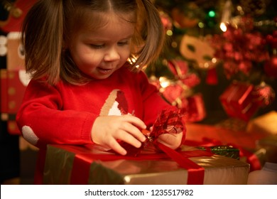 Cute baby unpacking gifts, smiling rejoices. Christmas tree in a cozy home. Fireplace. The girl is waiting for Christmas, New Year and holiday.