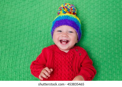 Cute baby in warm wool knitted hat on a green blanket. Autumn and winter clothing for young kids. Colorful knitwear for children. Adorable little boy ready for a walk on a cold fall day.