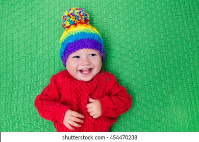 45bc754cef2 Cute baby in warm wool knitted hat on a red blanket. Autumn and winter  clothing