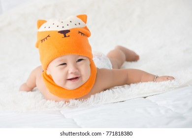Cute baby wearing diaper and fox head wool textile for infants. in white sunny bedroom. Nursery for children. Textile and bedding for kids.