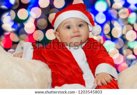 552842693 Cute baby wearing santa claus costume on a couch at home in christmas