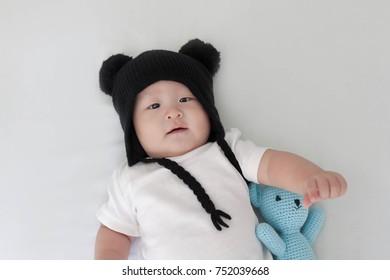 Cute baby wearing a yarn hat. Asian baby boy in winter hat. Portrait.