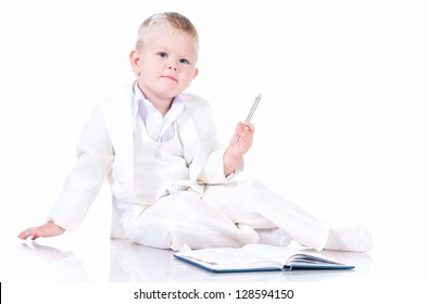 Cute baby in a white business suit with a diary