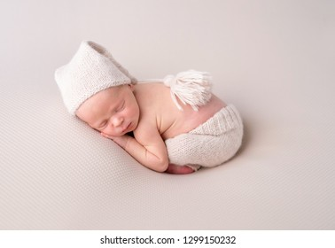 Cute baby in white knitted hat and pants sweetly sleeping