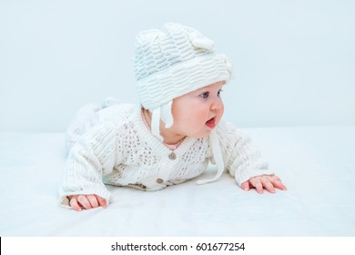 Cute baby in white knitted hat and sweater on a white background.