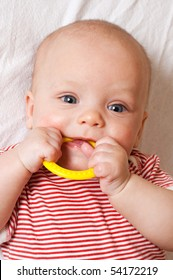 Cute baby with a yellow teething ring
