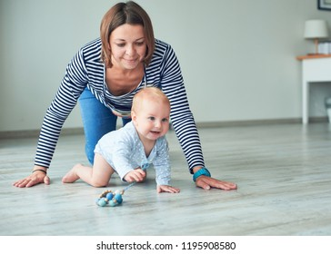 Cute baby and young mother crawling at home