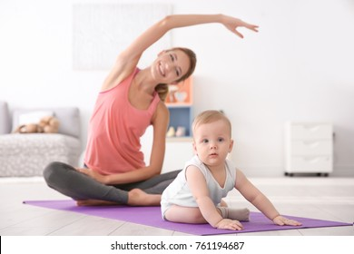 Cute baby and young mother doing yoga at home