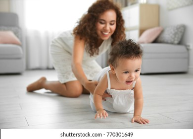 Cute baby and young mother at home