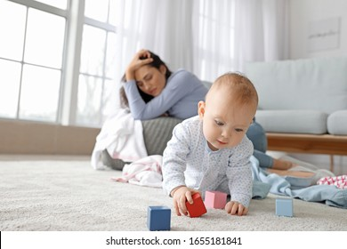 Cute baby and young woman suffering from postnatal depression at home