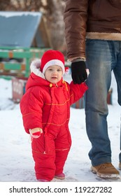 cute baby-daughter walk by the hand with dad  in winter