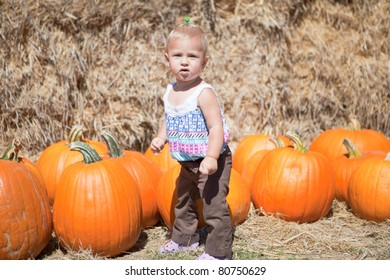 Cute baby-girl with big orange pumpkins