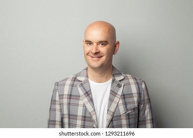 Cute bald man in a jacket and t-shirt shows against a gray wall