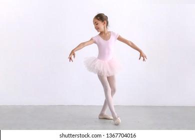 Cute ballerina little girl in pink tutu dance practice in the room, kid ballet concept.
