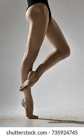 Cute ballerina is posing in the studio on the gray background. She stands on the right toe and holds left foot on the right leg. Girl wears a black leotard. Closeup. Vertical.