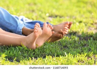 Cute barefoot children lying on grass outdoors