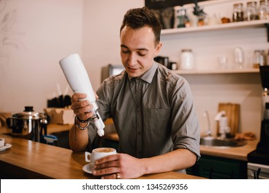 Cute barista make coffee latte adding cream in coffee shop cafe. Waiter pouring milky cream in cup of cappuccino. Details of barista preparing fresh cappuccino