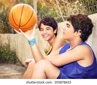 Cute basketball players sitting and resting in timeout, two active teen boys enjoying outdoor games, happy youth lifestyle