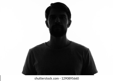 Cute bearded man in a T-shirt in the shadow on a light background