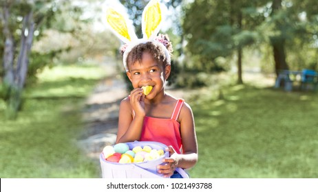 Cute and beautiful African American girl wearing bunny ears, eats with joy Easter marshmallow candy while holding Easter basket full of eggs. Girl sits in park outdoors in Spring. Text copy space.