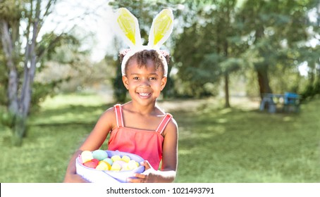 Cute and beautiful African American girl wearing bunny ears, looks at camera smiling while holding Easter basket full of eggs. Girl sits in park outdoors in Spring. Text copy space.