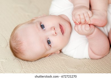 Cute beautiful baby with big eyes lies on the bed
