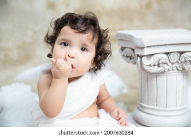 Cute beautiful baby. A mix of Chinese and Caucasian. Sitting on the chair and posing for the camera. Smiling, happy, and playing. Dressed in toga like a Greek god