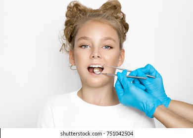 Cute, beautiful blonde young girl with nice teeth, is at the dentist