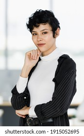 Cute and beautiful businesswoman in suit dress standing in the office and touc her chin with self-confident and elegant pose.
