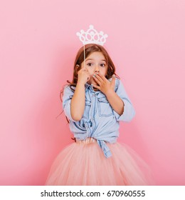 Cute beautiful carnival kid having fun isolated on pink background. Pretty little girl with long brunette hair, in tulle skirt, with white crown on head expressing wondering to camera